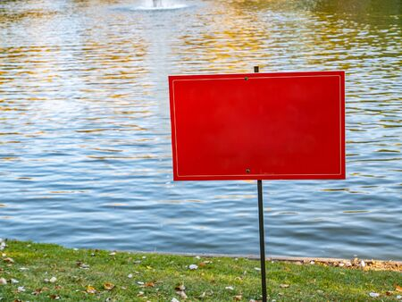 Red warning sign on the shore of a pond. Place for text.