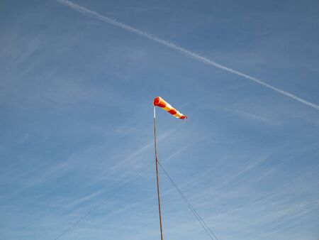 Wind direction indicator on the airfield. Navigation. Blue sky.