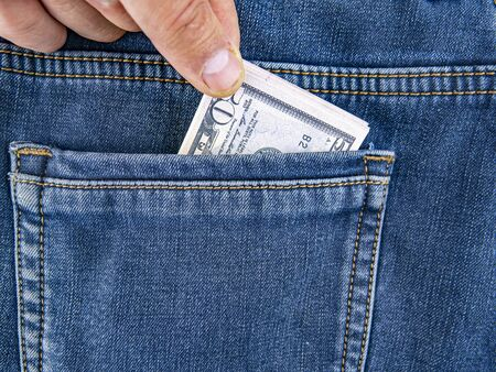 A hand takes money out of the back pocket of jeans. Theft. Robbery. Place for text. 免版税图像
