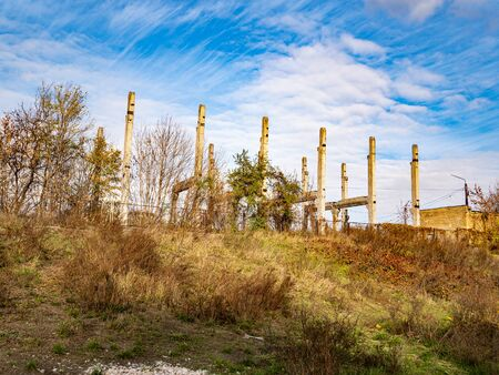 Abandoned construction site on a background of blue sky with clouds. Industrial landscape. 写真素材