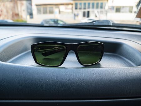 Sunglasses on a dashboard of a car. Place for text. Transport.