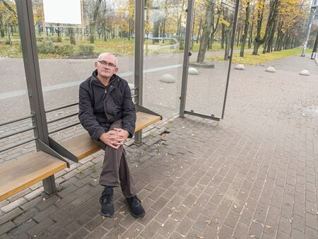 Gray-haired man at a public transport stop. A man with a bald head. People.