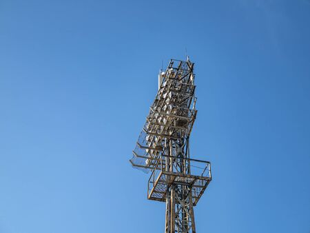 Tower stadium lighting against the blue sky. Industrial landscape. Place for text.