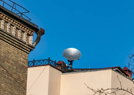 Satellite dish on the roof of the building against the blue sky. Technology. Place for text. Background image.