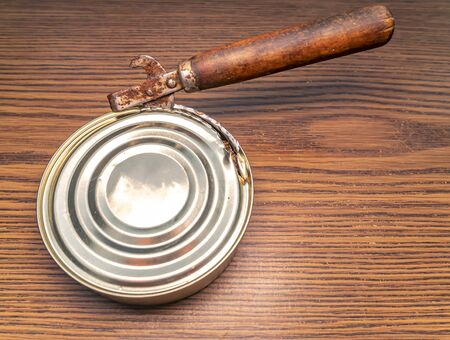 Tin can and can opener on a wooden table. Place for text. Background image.
