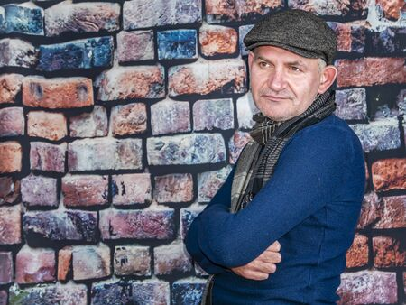A man in a cap against a brick wall. People. Place for text. Background image. Photo model. Fashion.