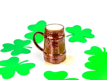 St. Patrick's mug of beer and clover leaves on a white background. St.Patrick 's Day. Place for text. Holiday.