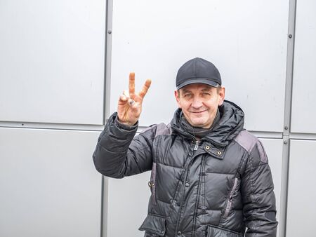 A man gesturing with a hand shows a victory sign on the street. People. Winter clothes. Place for text. City life