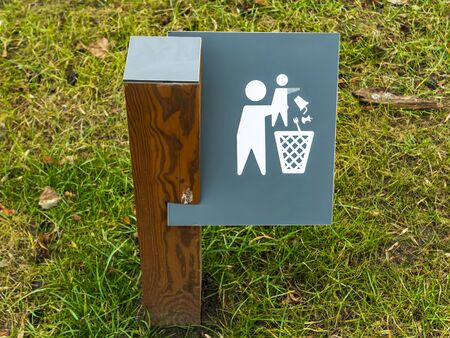 A warning sign about the rules of conduct in a public park. Background image. A place. for text. Trash bin.