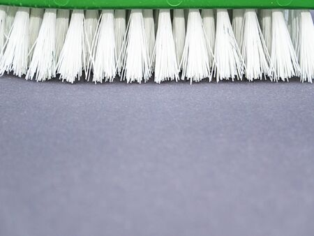 Clothes brush with white bristles on a gray background.