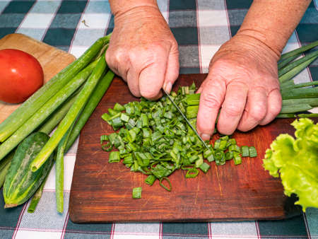 Slicing green onions with a knife on a cutting board. Green vegetable salad. Vegetables. Cook. Home kitchen. Vegetarian food. Recipe. Hands of a man. Vitamins