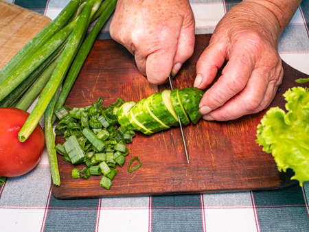 Cutting a vegetable a green cucumber with a knife on a cutting board. Green vegetable salad. Cook. Home kitchen. Vegetarian food. Recipe. Promotional photo. Hands of a man. Vitamins Archivio Fotografico