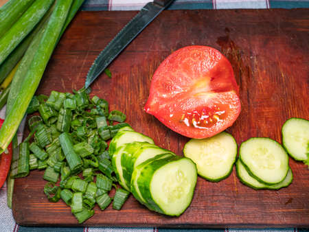 Slicing a red tomato with a knife on a cutting board. Green vegetable salad. Cook. Home kitchen. Vegetarian food. Recipe. Promotional photo. Hands of a man. Vitamins
