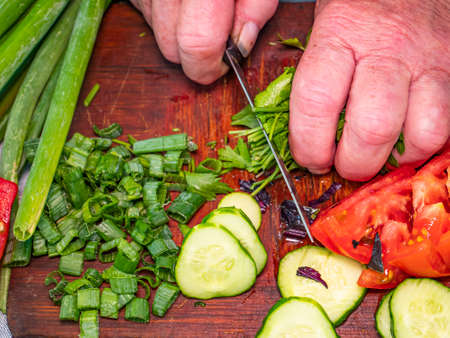 Slicing green parsley with a knife on a cutting board. Green vegetable salad. Vegetable. Cook. Home kitchen. Vegetarian food. Recipe. Promotional photo. Hands of a man. Vitamins Archivio Fotografico