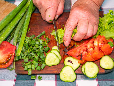Slicing green lettuce with a knife on a cutting board. Green vegetable salad. Vegetable. Cook. Home kitchen. Vegetarian food. Recipe. Promotional photo. Hands of a man. Vitamins