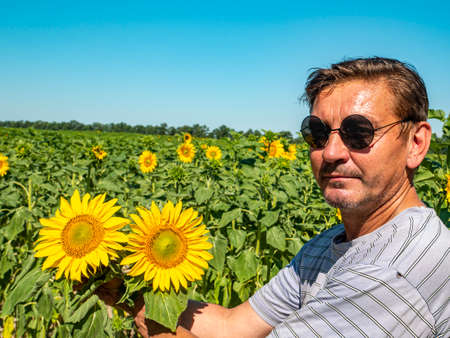 A man in sunglasses against the backdrop of a blooming field of sunflowers. Father's day. People Farm field. Agriculture. Advertising photo. Outdoors. Summer season. Place for your text. Poster