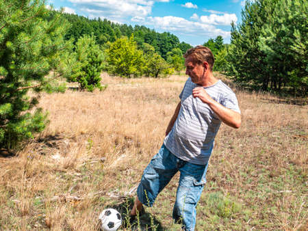 A man plays a soccer ball on a forest lawn. Tourist rest in the forest. Sport. Football match. Leisure activities by people. Place for your text. Background image. Sunny day. Pine forest. Archivio Fotografico