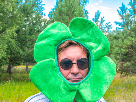 A man wearing a st patrick hat and sunglasses. St. Patrick 's Day. Festive party. Leisure activities by people in the forest. Nature. Picnic. Background image. Place for your text.