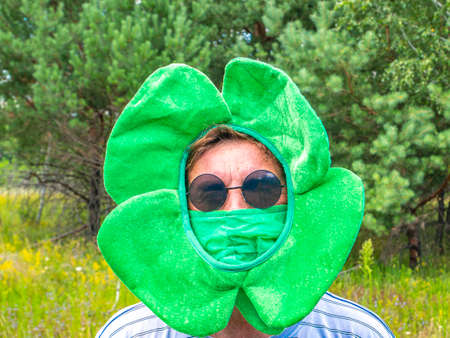 Saint patrick wearing a medical mask for coronavirus. St. Patrick 's Day. The man. Festive quarantine party. Leisure activities by people in pademia. Nature. Picnic. Medicine. Clover leaf.