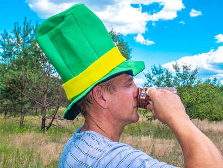 A man in a st patrick hat drinks from a beer mug. St. Patrick 's Day. Festive party. Leisure activities by people in the forest. Nature. Picnic. Background image. Place for your text. Blue sky. Archivio Fotografico
