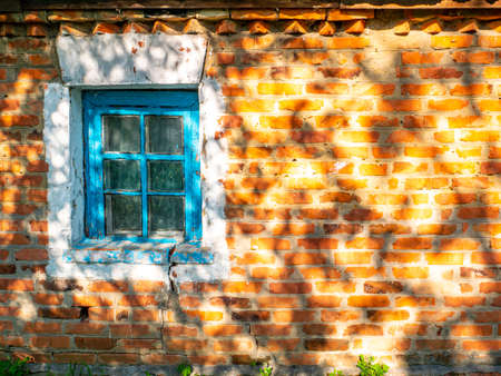 Old window on a background of a red brick wall. Country house. Place for text. Template. Poster. Building sector. The shadows of the leaves on the wall. Sunlight. On the street. Background image.