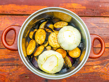 Blue eggplant vegetables and squash in a kitchen saucepan.