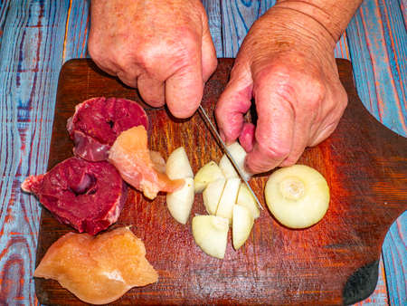 Cutting onions with a knife for preparing a meat dish.