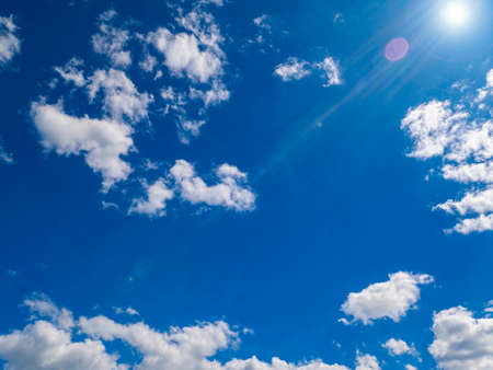 Sun on a background of blue sky with clouds. Sun rays with glare. Space. Stratosphere. The ozone layer of the earth. Cloudy landscape. Background image. Template for text. Poster. Stock fotó
