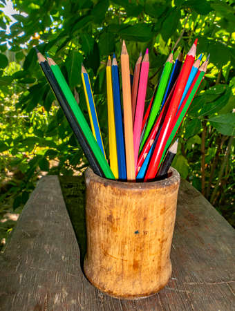 Colored pencils for drawing in a wooden glass. School drawing lesson. Eraser. Place for your text. Template. Background Image. Poster. Office supplies.