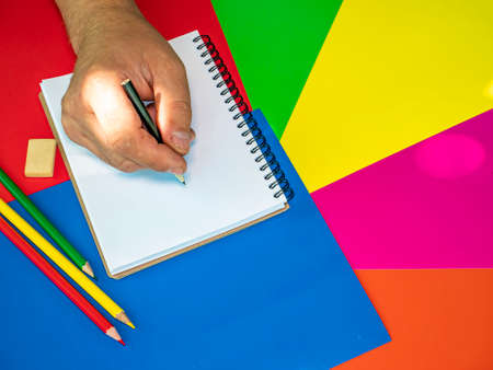 We draw in a notebook with a pencil. School drawing lesson. Eraser. Place for your text. Human hand. Template. Background Image. Poster. Sheets of colored paper. Stock fotó