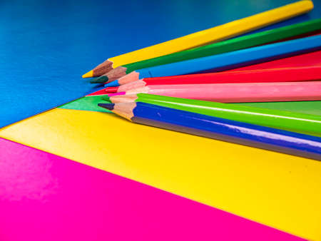 Colored pencils for drawing on the table. Multicolored background. Sharpened pencil. School drawing lesson. Eraser. Place for your text. Template. Background image. Poster. Sheets of colored paper.