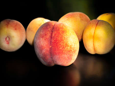Ripe peach fruit on a black background. Food photo. Harvesting. Peach juice. Agriculture. Advertising photo of a shop window of a fruit shop. Place for your text. Background image. Template. Poster.