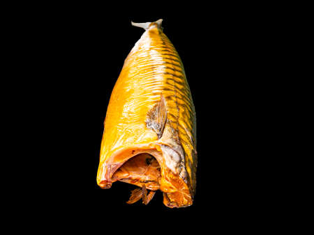 Smoked mackerel fish on a black background. Salted mackerel fish. Canned food. Food photo. Recipe. Menu of dishes. Vegetarian food. Home kitchen. Fishing. Background image. Place for your text.