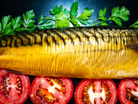Smoked mackerel fish with tomatoes on a black background. Salted mackerel fish. Green parsley. Canned food. Food photo. Recipe. Menu of dishes. Vegetarian food. Home kitchen. Fishing. Stock fotó