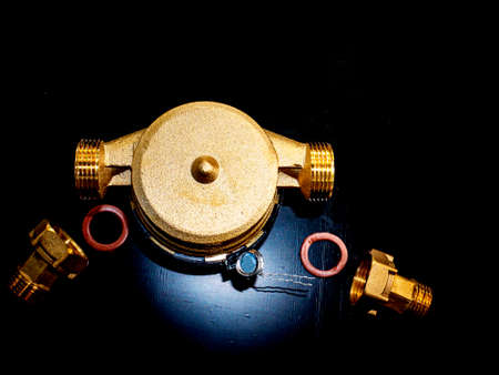Water meter with threaded connection for nuts. Black background. Plumbing equipment. Plumbing repair. Plumbing repairman. Pipeline. Background image. Place for your text.
