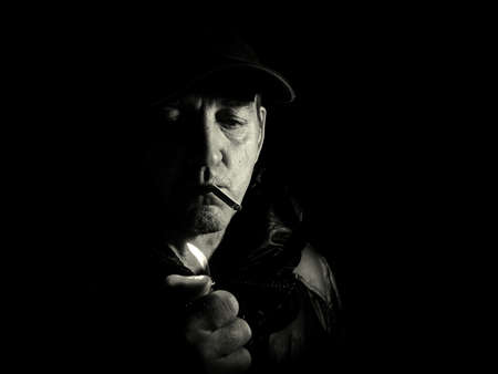 A man lights a cigarette with a lighter in the dark. Smoking cigaoretu. Lighter in hand. Man in the dark at night. Portrait of a man. Unshaven. Cap on the head. Black and white photography.