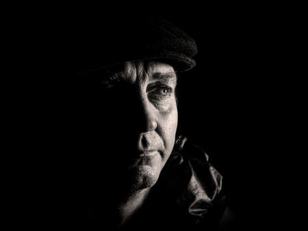 A man looks into the darkness a black and white photograph. Male look. Look into the distance. A man in the dark at night. Portrait of a man. Unshaven. Fathers day. Cap on the head.