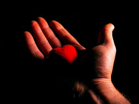 Heart symbol of valentines day in hand on black background. Stock Photo