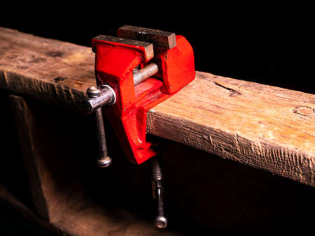Locksmiths tool metal vise fixed on a wooden table. Stock fotó