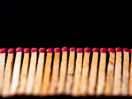 Wooden matches with red sulfur heads on a black background.