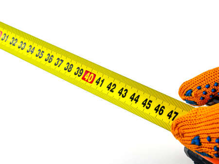 Measuring tape in the hands of a worker. Roulette measuring tool. Ruler for measurements. Work orange protective gloves. Centimeter on a white background. Inches and centimeters. Hand.