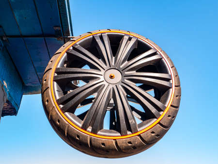 A car wheel attached to the roof of a building against the blue sky. Tire service. Car tire. Vehicle spare part. Customer Service. Repair and service. Metal detail. Mechanic repairman. Master. Stock fotó