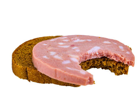 Bitten black bread sandwich with pork sausage and lard on a white plate. Black bread. Meat sausage. Pork fat. Pork product. Fatty food. Not vegetarian food. Meat dish. Home kitchen. White background.