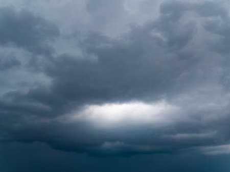 Sunlight through a thundercloud in the sky. Thunderclouds. Sunlight. Gloomy sky. Hurricane coming. Weather cyclone. Weather forecast. Rainy season. Background image.