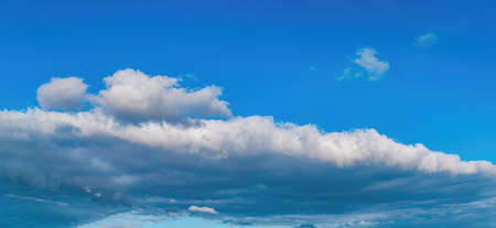 Panoramic photo of the sun against a blue sky with white clouds.