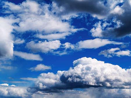 White cloud against blue sky in sunlight.