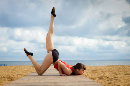 Young woman doing stretching on a beach  photo