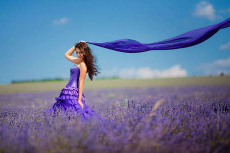 Portrait of beautiful romantic woman in fairy field of lavender with a colored tissue  photo