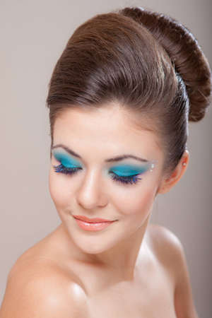 close-up portrait of beautiful caucasian young woman with blue glamour make-up photo
