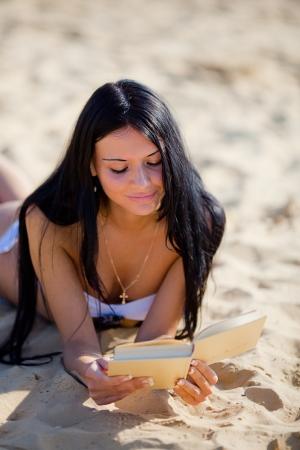 Mujer hermosa joven que se est� relajando y leyendo el libro en la playa Foto de archivo - 18726007